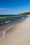 Plage blanche de sable et eau verte de mer baltique Photos stock