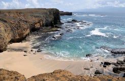 Plage blanche de sable par la falaise Photographie stock libre de droits