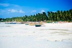 Plage blanche tropicale de sable avec les palmiers verts et les bateaux de pêche garés dans le sable Paradis exotique d'île Photographie stock libre de droits