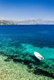 Plage bleue claire chez Korcula Croatie avec le bateau photographie stock libre de droits