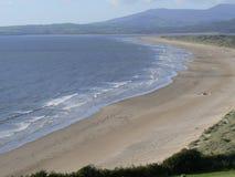 Plage côtière au loin abandonnée avec la marée basse et les dunes de sable Photos stock