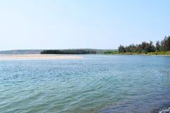 Plage calme d'articles avec l'eau bleue propre, des arbres et une île Photographie stock