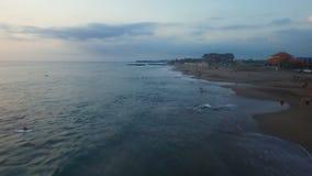 Plage d'océan avec des surfers et des touristes à l'antenne de coucher du soleil banque de vidéos
