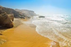 Plage d'océan en été sous le ciel bleu Vagues enroulant sur le rivage rocheux Images stock