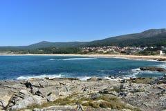 Plage dans une baie avec la forêt et la petite montagne Roches, vagues et petit village côtier Jour ensoleillé, mer bleue avec la photo libre de droits