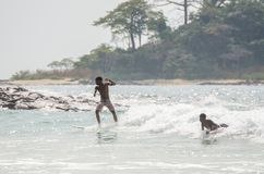 Plage de Bureh, Sierra Leone - 11 janvier 2014 : Deux jeunes garçons africains non identifiés surfant seulement à la tache de res Image libre de droits