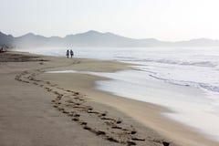 Plage de Costa Rei en Sardaigne et un couple marchant le long de lui Image stock