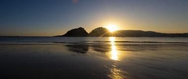 Plage de Hondarreta, le soleil derrière les montagnes dans la ville de San Sebastian Photos stock