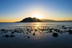 Plage de Hondarreta, le soleil derrière les montagnes dans la ville de San Sebastian Images libres de droits