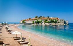 Plage de luxe de sable de Sveti Stefan avec des chaises et des parapluies de chaise longue Images libres de droits