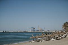Plage de Malagueta dans un jour ensoleillé, avec des chaises de plate-forme et des parapluies sur le sable Photos libres de droits