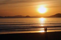 Plage de marche de couples au coucher du soleil Photographie stock libre de droits
