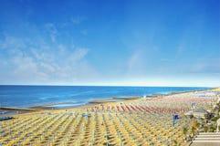 Plage de mer avec le début de la matinée de parasols Photographie stock