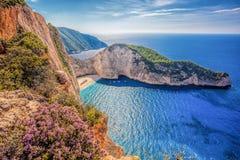 Plage de Navagio avec le naufrage et les fleurs contre le coucher du soleil sur l'île de Zakynthos en Grèce image stock