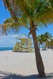 Plage de sable avec les palmiers et la tour de lifegard Photos stock