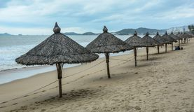 Plage de sable avec les parapluies en bois photographie stock