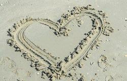 Plage de sable de forme de coeur, bord de la mer avec de l'eau et coquilles Images libres de droits