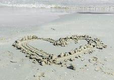 Plage de sable de forme de coeur, bord de la mer avec de l'eau et coquilles Photo stock