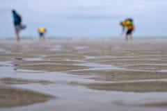 Plage de sable de mer avec les silhouettes brouillées des personnes Photos stock