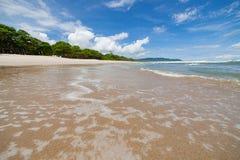 Plage de sable de vagues et jour ensoleillé de nuages photo stock