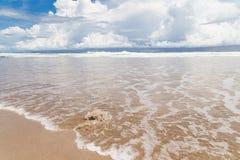 Plage de sable de vagues et jour ensoleillé de nuages images stock