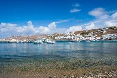 Plage de village de pêche dans Mykonos, Grèce Mer et bateaux sur le ciel bleu nuageux Maisons blanches sur le paysage de montagne photos stock