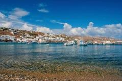 Plage de village de p?che dans Mykonos, Gr?ce Mer et bateaux sur le ciel bleu nuageux Maisons blanches sur le paysage de montagne images libres de droits