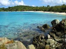 Plage des Caraïbes encadrée par des palmiers et des roches Photographie stock libre de droits