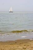 Plage ensoleillée avec le bateau à voile dans la distance Photos stock