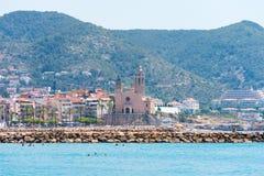Plage et église pierreuses de Sant Bartomeu et de Santa Tecla dans Sitges, Barcelone, Catalunya, Espagne Copiez l'espace pour le  Photos stock