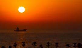 Plage et bateau exotiques au coucher du soleil Photographie stock libre de droits