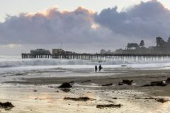 Plage et quai de Capitola dans les nuages orageux coucher du soleil et la silhouette de surfers image stock