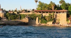 Plage et restaurant de Mermerli avec les murs de ville dans Antalyas Oldtown Kaleici, Turquie Photos stock