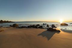 Plage et roches pendant le coucher du soleil Photographie stock