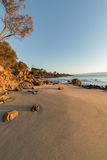 Plage et roches pendant le coucher du soleil Image libre de droits