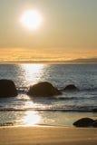 Plage et roches pendant le coucher du soleil Photos stock