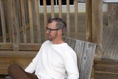 Plage la Caroline du Sud de folie, le 17 février 2018 - équipez se reposer dans la chaise en bois écoutant la conversation Photographie stock