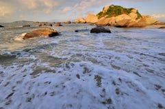 Plage large de mer avec la roche dans le lever de soleil Photos stock
