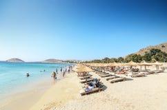 Plage large de sable avec des touristes, des parapluies et des lits dans Mykonos, Grèce Images stock