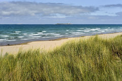 Plage, le Northumberland, Angleterre - dans le phare de fond Images stock