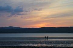 Plage marchant dans le coucher du soleil Photos libres de droits