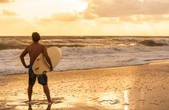 Plage masculine de lever de soleil de coucher du soleil de surfer et de planche de surf d'homme Photo libre de droits