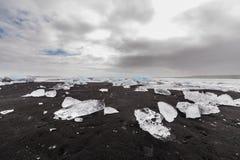 Plage noire avec de la glace près d'une lagune Jokullsarlon de glacier en Islande Photographie stock libre de droits