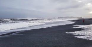 Plage noire de sable le jour orageux l'islande Images stock