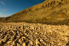 Plage pierreuse et basse falaise de grès photographie stock libre de droits