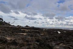 Plage rocheuse avec le ciel nuageux Photographie stock