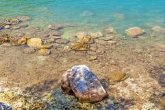 Plage rocheuse de littoral avec un vieux mur en pierre, les buissons et les arbres o Photographie stock libre de droits