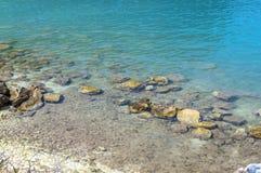 Plage rocheuse de littoral avec un vieux mur en pierre, les buissons et les arbres o Image stock