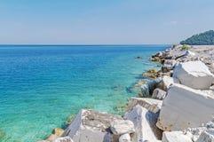 Plage rocheuse de littoral avec un vieux mur en pierre, les buissons et les arbres o Photographie stock