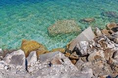 Plage rocheuse de littoral avec un vieux mur en pierre, les buissons et les arbres o Photos libres de droits